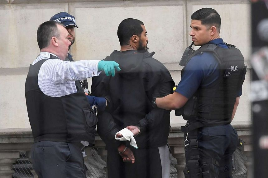 A man is held by police in Westminster after an arrest was made on Whitehall in central London, Britain, April 27, 2017.