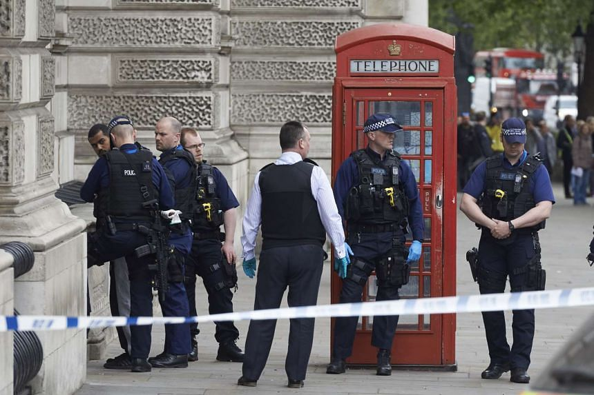 Firearms officers from the British police detain a man (left) on Whitehall near the Houses of Parliament in central London on April 27, 2017 before the man is taken away by police.