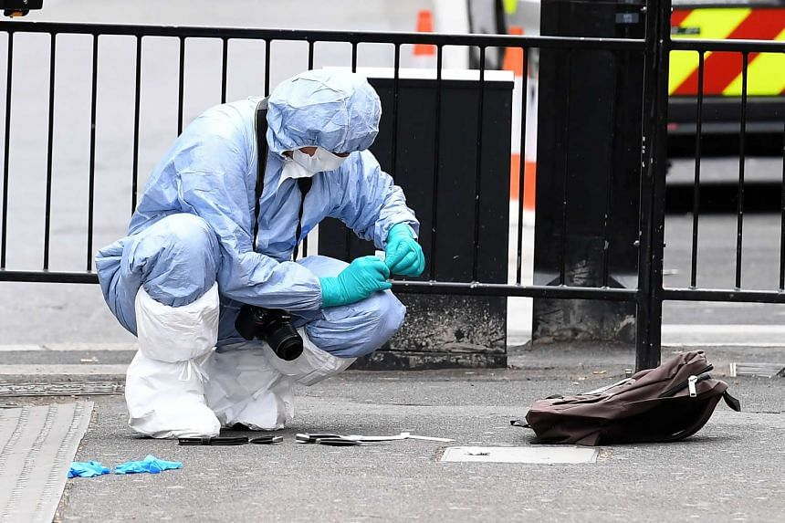 A British police forensics officer collects evidence on Whitehall near the Houses of Parliament in central London on April 27, 2017, at the scene where a man was detained and taken away by police.