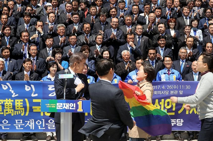 """Civic activists with a rainbow flag, known as the """"gay pride"""" flag, protesting to presidential front runner Moon Jae In over his stance against homosexuality, as he campaigned in front of the National Assembly in Seoul, South Korea, yesterday."""