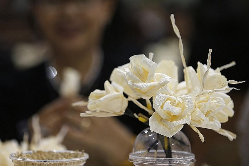 Volunteers making flowers at the Thai-Japan Youth Centre in Bangkok yesterday. The blooms will be used in the royal crematorium for the late Thai King Bhumibol Adulyadej's cremation ceremony. Three million flowers are being made, and will be given to