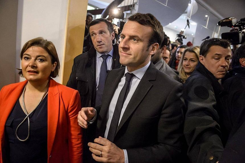 French presidential election candidate Emmanuel Macron (centre) arrives to a meeting with the representatives of the Whirlpool inter-union, at the Chamber of commerce in Amiens, northern France, on April 26, 2017.