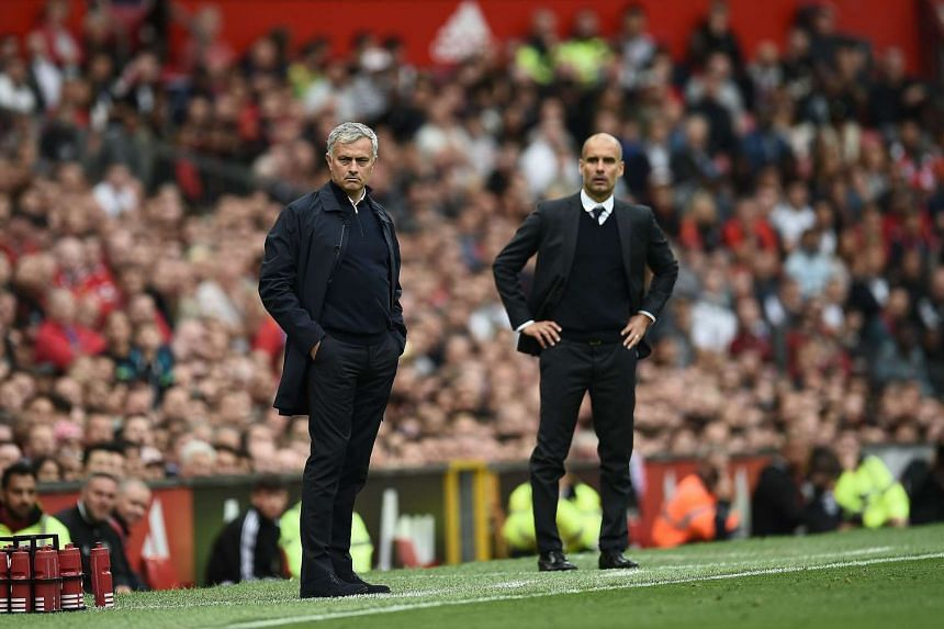 Jose Mourinho (left) and Pep Guardiola watching from the touchline during the English Premier League football match between Manchester United and Manchester City.