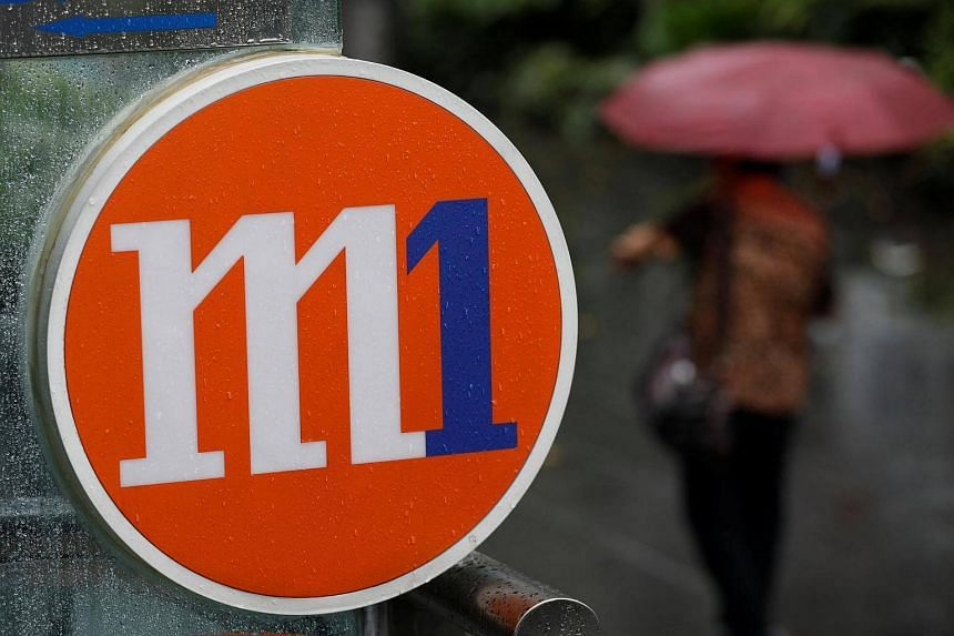 A woman with an umbrella passes an M1 sign in Singapore on April 7, 2017.