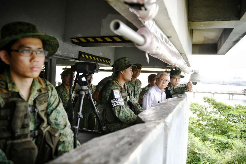 President Tony Tan Keng Yam taking a tour of the observation tower in Jurong Island yesterday. He visited operationally ready national servicemen from the 823rd Battalion of the Singapore Infantry Regiment on Jurong Island.