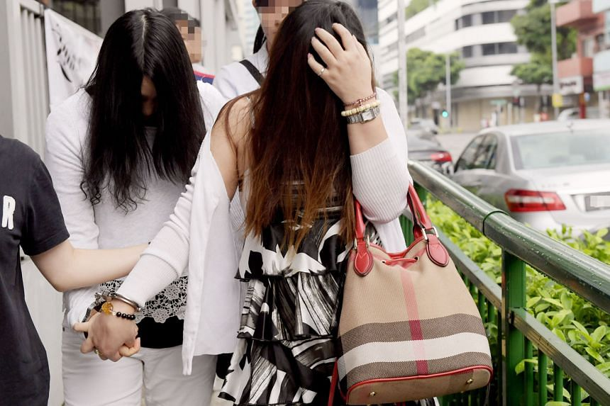 Two women from a TCM outlet in Rangoon Road being taken away after a police raid. They were among six foreign women who were found yesterday to be offering sexual services in massage parlours.