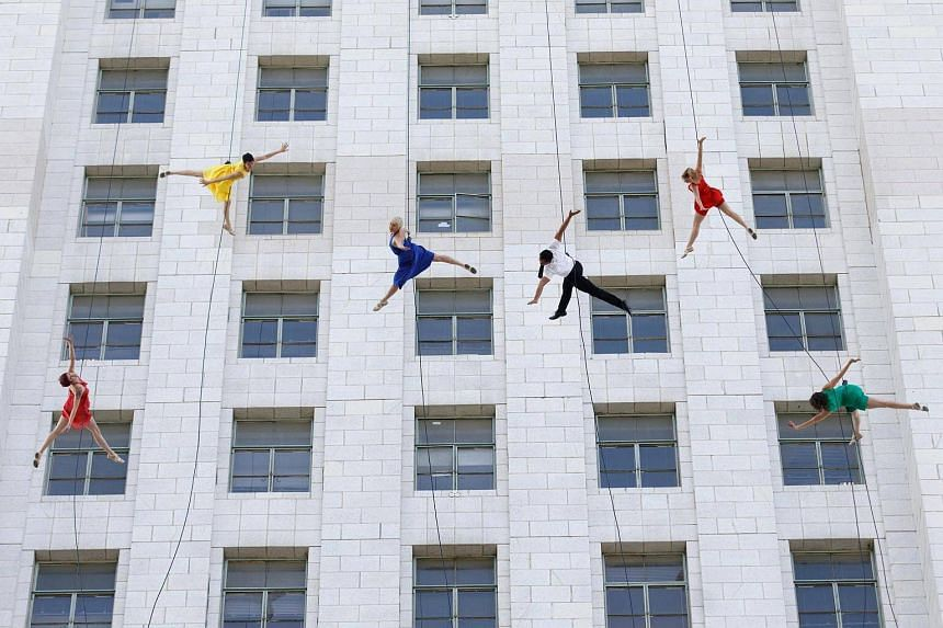 """Aerial dancers performing on the side of the City Hall building on """"La La Land Day""""."""