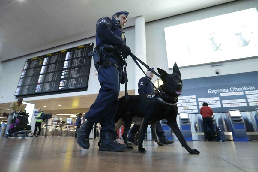 Police officers patrol the Brussels airport ahead of a commemoration ceremony, March 22, 2017.