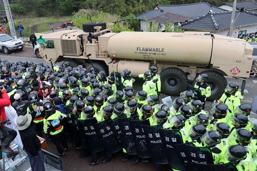 Protesters and police standing by as trailers carrying US Thaad missile defence equipment enter a deployment site in Seongju, early on April 26, 2017.