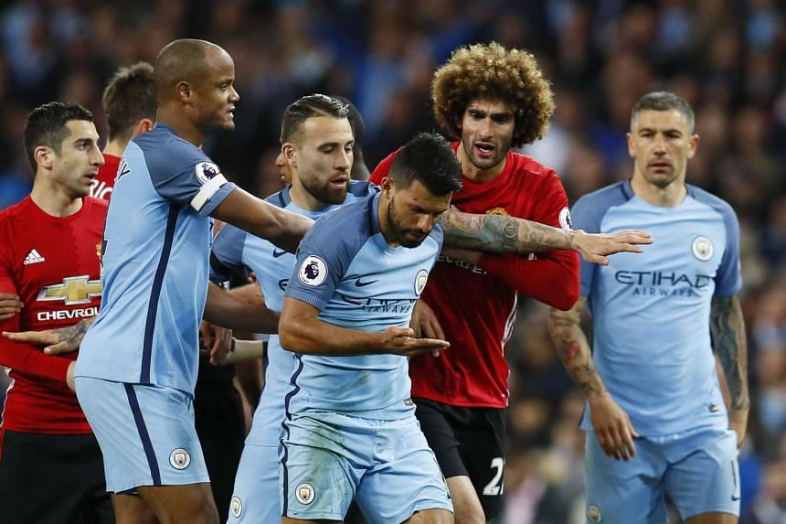 Manchester United's Marouane Fellaini with Manchester City's Sergio Aguero after being sent off by referee Martin Atkinson.