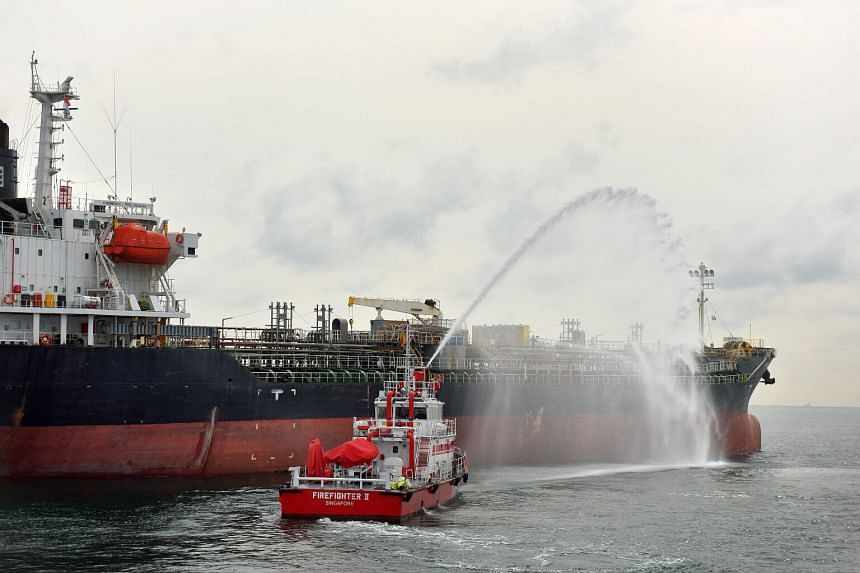 A Singapore Civil Defence Force (SCDF) Marine Command vessel spraying water over the contamination zone in a chemical spill simulation exercise held by the Maritime and Port Authority (MPA).