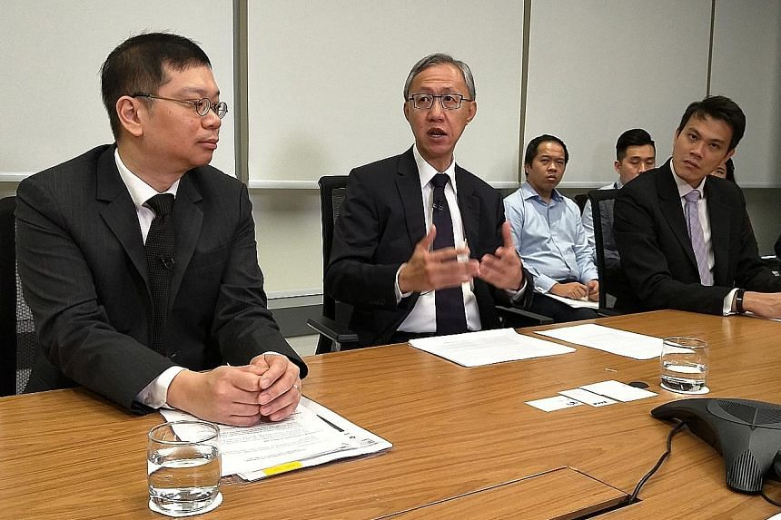 """Professor Tan Cheng Han (centre), RegCo chairman, with CEO Tan Boon Gin (left) and regulatory development head Chew Chin Yee at a press briefing yesterday. Prof Tan said he will bring """"a pair of fresh eyes"""" to the review process."""