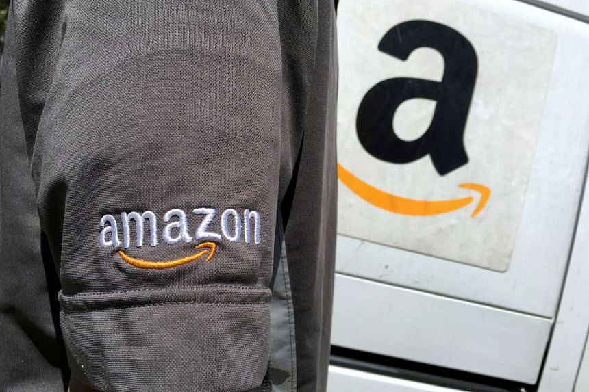 An Amazon.com Inc driver stands next to an Amazon delivery truck in Los Angeles.