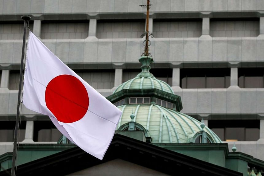 A Japanese flag flutters atop the Bank of Japan building in Tokyo, Japan.