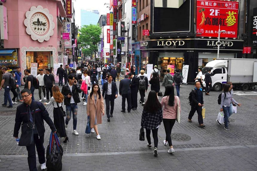 People walking in the popular Myeongdong shopping district in Seoul.