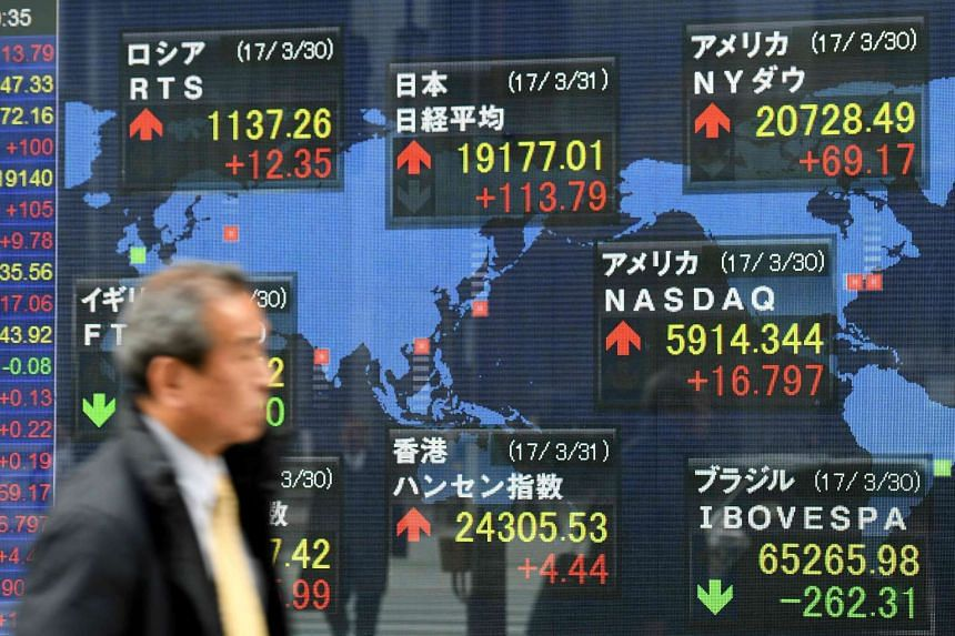 A passerby walks past a stock indicator at the window of a security company in Tokyo on March 31, 2017.
