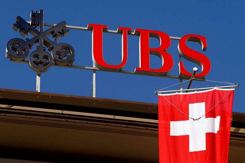 Switzerland's national flag flies under the logo of Swiss bank UBS in Zurich.