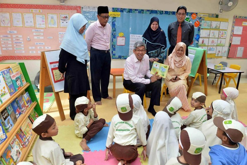 Associate Professor Dr Yaacob Ibrahim (seated centre), Minister for Communications and Information and Minister-in-charge of Muslim Affairs, reading a story book to some kindergarten children from Al-Muttaqin Mosque on June 30, 2016.
