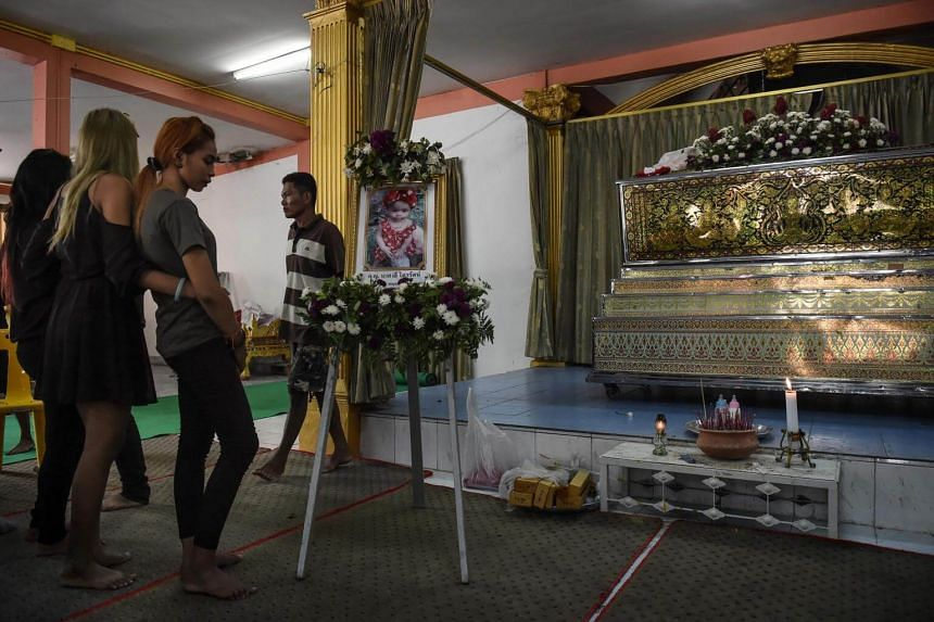 Jiranuch Trirat (3rd from left) is comforted by friends as she looks at a photograph of her 11-month-old daughter Natalie during the last funeral rites at a temple in Phuket on April 29, 2017.