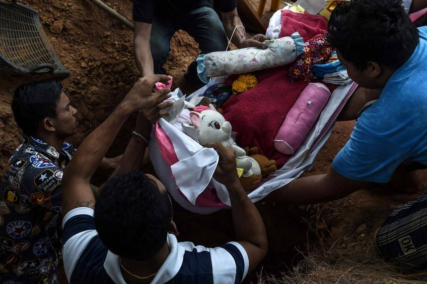 The body of 11-month-old girl Natalie is carried into her grave by male relatives in Phuket on April 29, 2017.