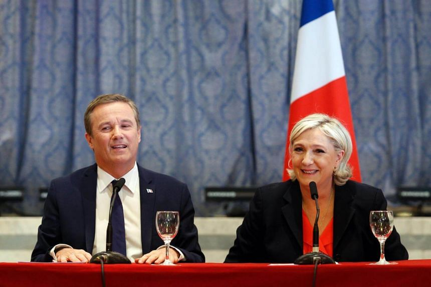 Former French presidential election candidate Nicolas Dupont-Aignan (left) and French presidential election candidate Marine Le Pen react as they speak during a joint statement at the Front National party headquarters in Paris, on April 29, 2017.