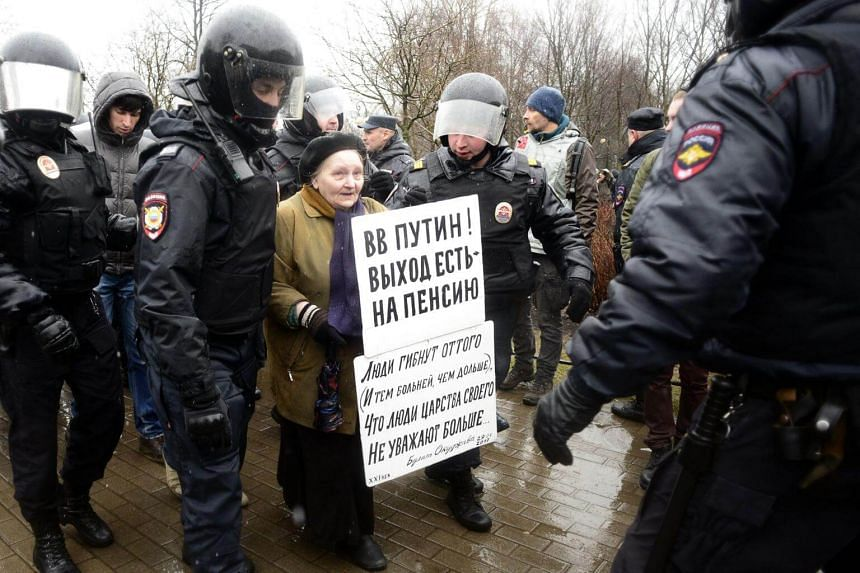 Police officers detain an activist during a protest rally calling for Vladimir Putin not to stand for a fourth term in 2018 in Saint Petersburg on April 29, 2017.