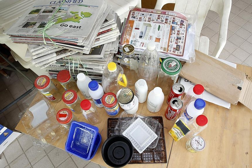 Retiree Peter Lo started a recycling drive in seven zones in his Sembawang neighbourhood that is still ongoing to this day. The items freelance writer Olivia Choong (above) collects in her home for recycling include used newspapers, milk cans and pla
