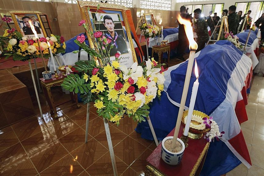 The rangers' coffins draped with the Thai national flag at their funeral yesterday.