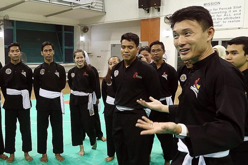 Parliamentary Secretary for Ministry of Culture, Community and Youth, Baey Yam Keng (right), donning silat attire while visiting the Singapore national silat exponents - led by world champion Shakir Juanda (centre) - as well as the national sepak tak