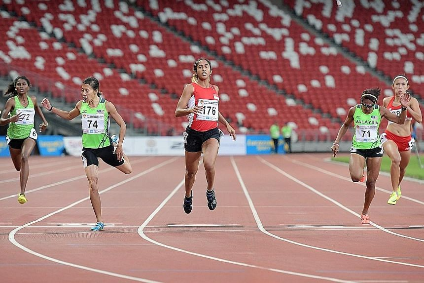 Shanti Pereira (centre) crossing the finish line in 23.87sec to win 200m gold at the Singapore Open Track and Field C'ships at the National Stadium. Her timing meets the SEA Games qualifying mark of 23.92sec.