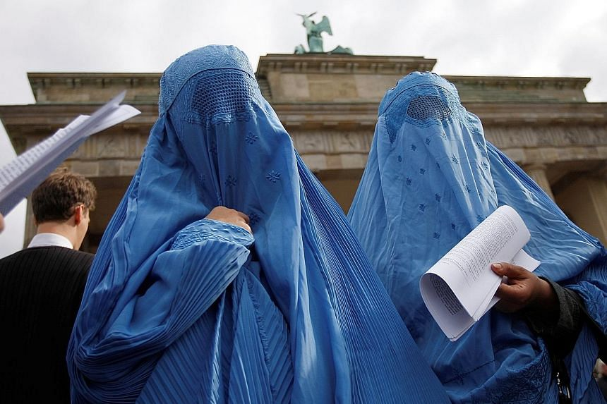 Burqa-clad protesters in front of the Brandenburg Gate in Berlin. German lawmakers yesterday passed new security measures, including a partial ban on the full-face Islamic veil.