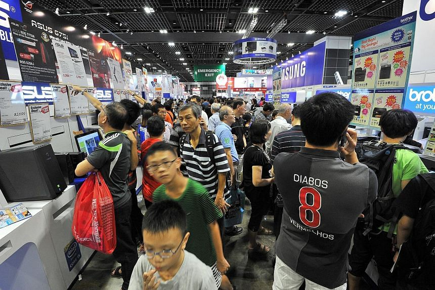 Crowds at an IT fair in Singapore. Consumer loans inched up 0.2 per cent year on year to $251.37 billion last month.