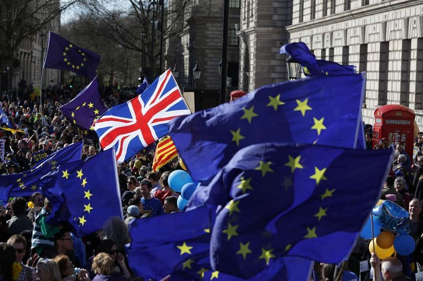 Demonstrators wave EU flags and Union Flags in Parliament Square during an anti-Brexit, pro-European Union march, on March 25, 2017.