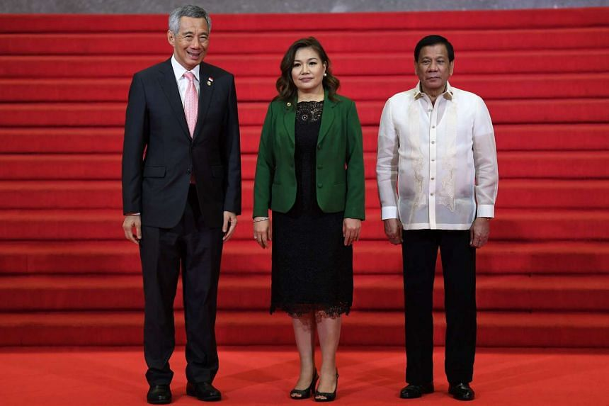 PM Lee (left) posing with Philippine President Rodrigo Duterte (right) and his partner Honeylet Avancena (centre) upon his arrival at the opening ceremony of the Asean leaders' summit in Manila, on April 29, 2017.