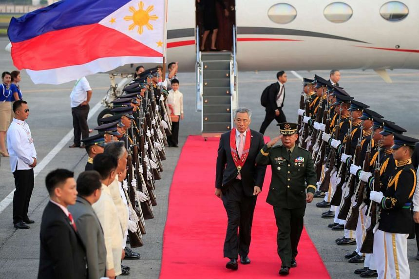Singapore Prime Minister Lee Hsien Loong reviewing the honour guard on arrival at the <NO1>Manila International airport<NO>Ninoy Aquino International Airport in Manila yesterday.
