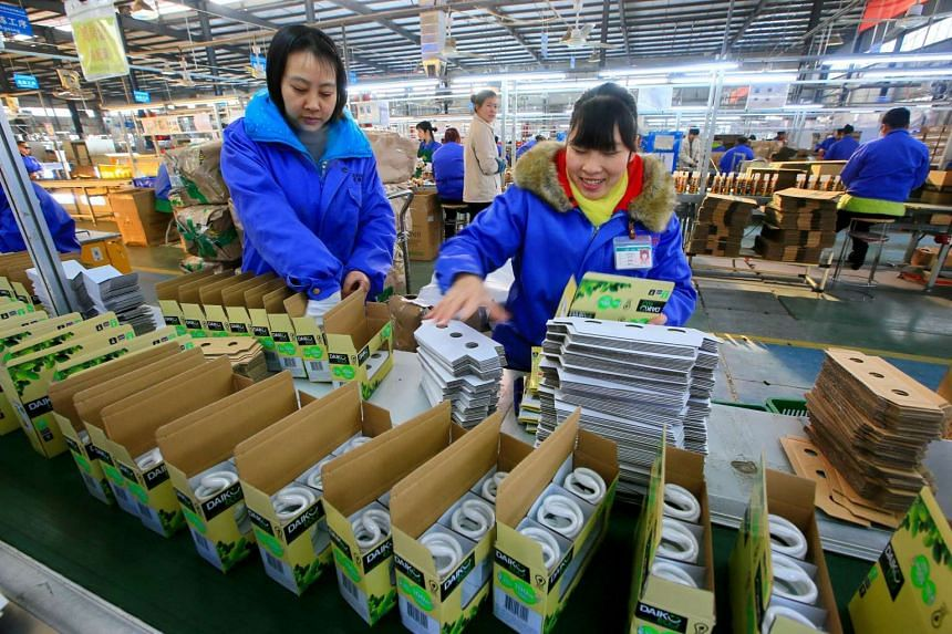 Chinese employees working on an energy-saving bulb production line at a lighting factory in Suining, southwest China's Sichuan province on Feb 28, 2017.