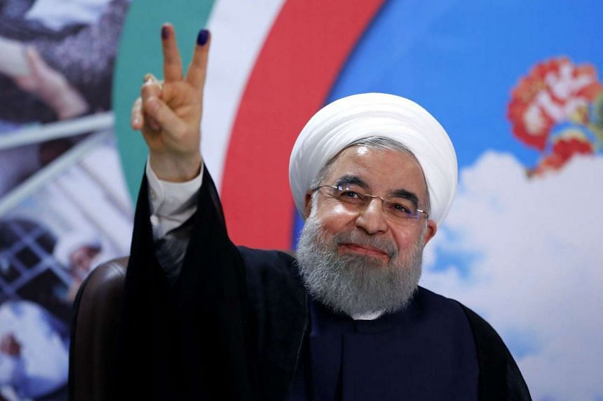 Iranian President Hassan Rouhani gestures to the camera after registering to run for re-election.
