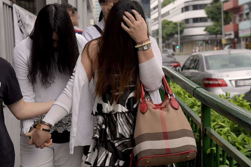 Two women from a TCM outlet in Rangoon Road being taken away after a police raid.
