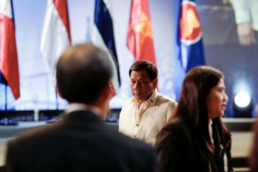Philippine President Rodrigo Duterte (centre) arrives for the opening ceremony.