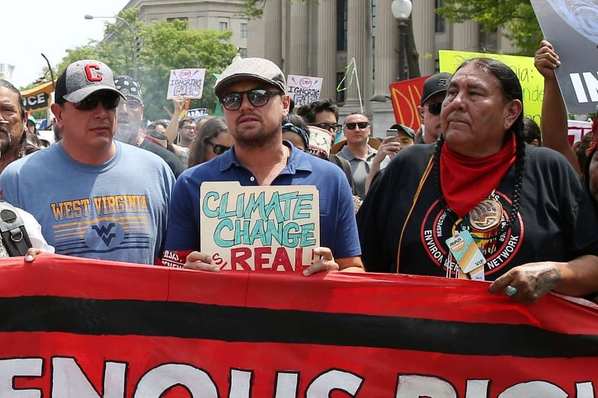 """DiCaprio (centre) held a sign that read """"Climate change is real."""""""