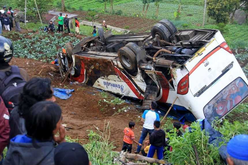 Residents looking at the wreckage of a bus after it tumbled down a slope, in Cianjur, Indonesia, on April 30, 2017.