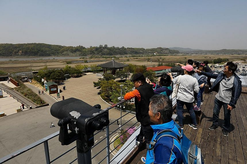 From the Odusan Unification Observatory near the Demilitarised Zone (DMZ) in Paju, South Korea, yesterday, visitors can see the North Korean village of Gaepung-Gu. North Korea is believed to have tested a medium-range missile, known as KN-17, but it