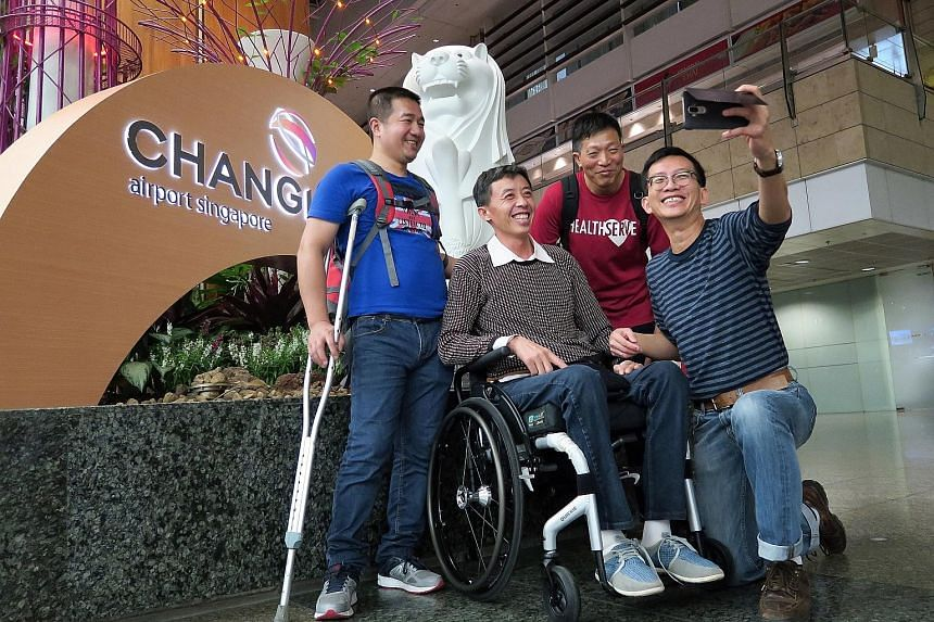 Mr Meng breaking into a rare smile while taking a wefie with manager Jeffrey Chua (holding camera) and volunteers Zhang Xihong (left) and Wang Qingguo at Changi Airport Terminal 2 Mr Meng being helped by a stewardess into his wheelchair upon arrival