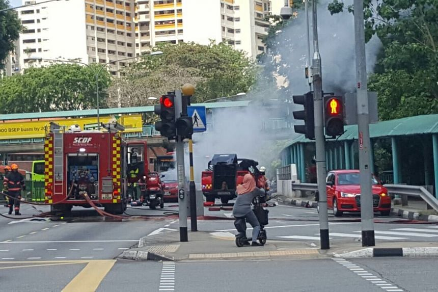 SCDF personnel attempting to put out a fire after a Trans-Cab taxi exploded along Commonwealth Avenue, on April 30. 2017.