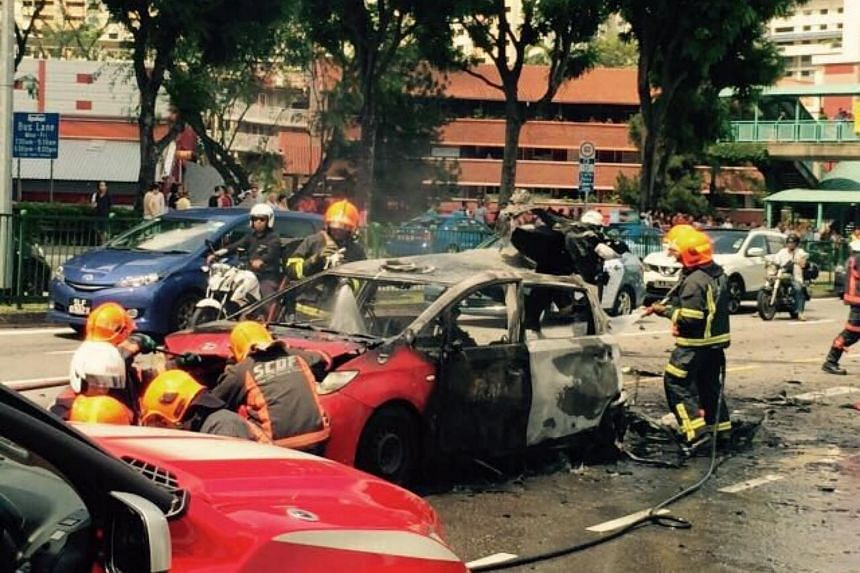 SCDF personnel examining the wreckage of the Trans-Cab taxi after it exploded, on April 30, 2017.