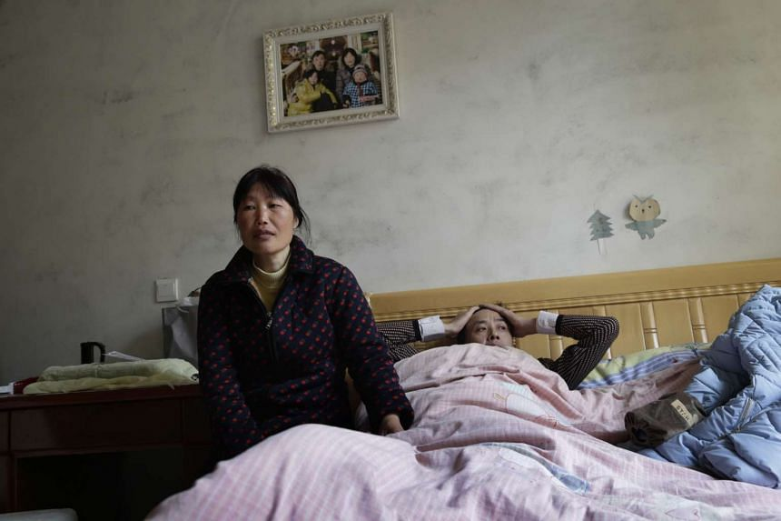 Mr Meng Xiangbo (right), 39, and his wife Yuan Jie, 43, in pensive mood on his first day back at home in Shimen village in Jiangsu province, China.