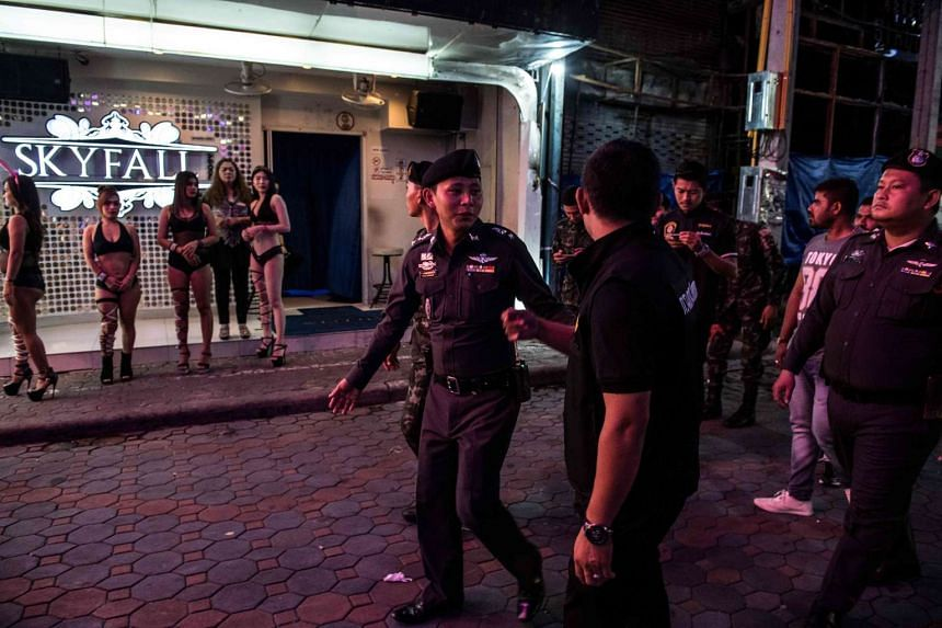 Policemen and soldiers pass young women enticing customers to enter a bar, as they patrol Walking Street in Pattaya on March 29, 2017.