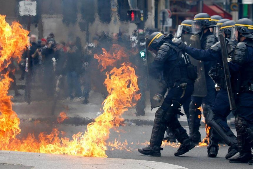 French CRS officers shielding themselves from flames during clashes in Paris on May 1, 2017.