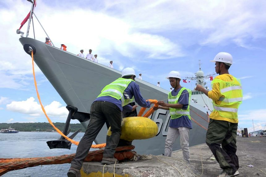 Port workers securing Chinese Navy warship Chang Chun at a port in Davao city.