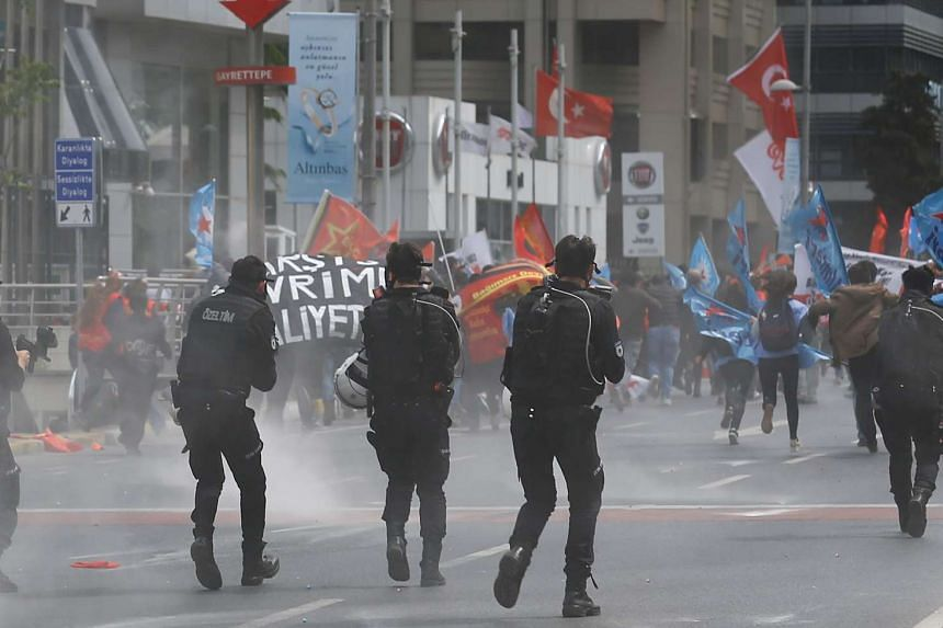 Protesters run as Turkish riot police launch tear gas grenades during a march to Taksim Square.
